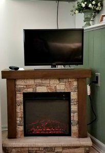 Electric Fireplace and flat screen tv, amenities which guests staying in our Log Cabin room can enjoy