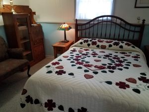 A photo of Lancaster Rose, Queen Sized bed with beautiful Amish appliqued quilt.