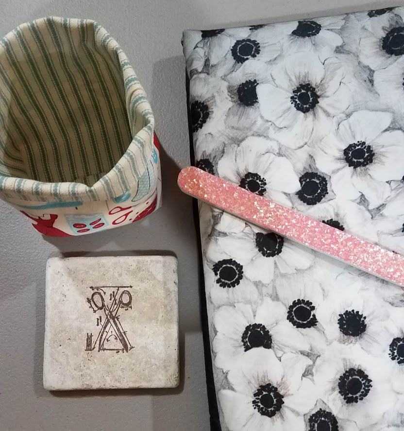 a photo showing the gifts that the June Sew Campers received.  Clockwise from top left corner is a thread catcher, the Mily fabric, an emery board and a sewing themed coaster.