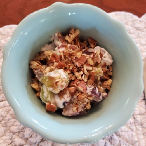 a bowl with a serving of grape salad topped with chopped pecans and served as the starter to breakfast at Carriage Corner B&B